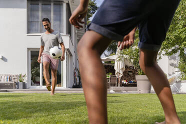 Father and son playing football in garden - DIGF07792