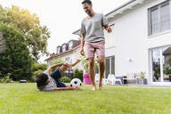 Father and son playing football in garden - DIGF07795