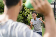 Father and son playing with american football in garden - DIGF07798