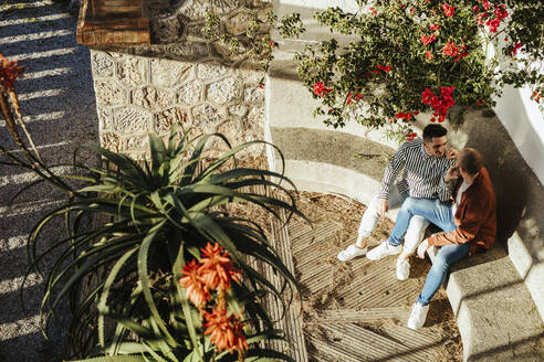 Gay couple sitting on a step outdoors surrounded by flowers - LJF00493