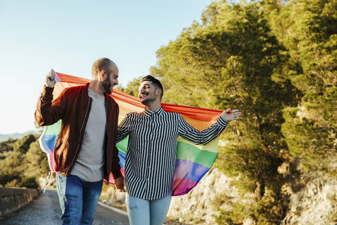 Happy gay couple with gay pride flag on a road in the mountains - LJF00502
