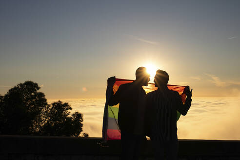 Silhouette of gay couple with gay pride flag in backlight - LJF00505