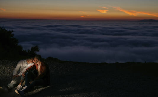 Gay couple kissing in the mountains above the clouds at sunset - LJF00517