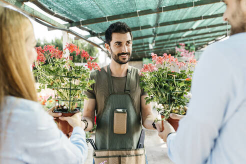 Smiling worker in a garden center showing plants to customers - JRFF03449