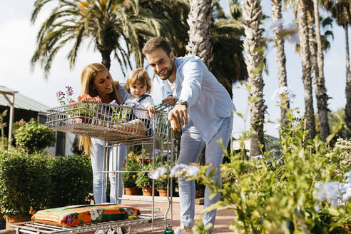 Happy family buying plants in a garden center wth the daughter in shopping cart - JRFF03458