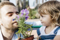 Father and daughter smelling at flower in a garden center - JRFF03461