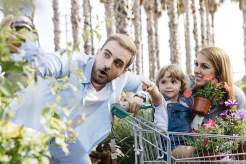 Family buying plants in a garden center wth the daughter in shopping cart - JRFF03470