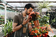 Worker in a garden center smelling at a flower - JRFF03476