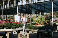 Mother, father and daughter walking around in a garden center - JRFF03482