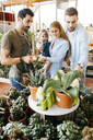 Shop assistant in a garden center advising customers - JRFF03488