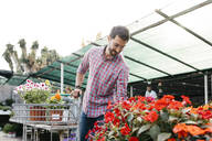 Customer of a garden center choosing a flower - JRFF03506