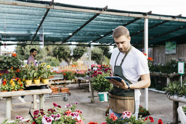 Worker in a garden center using a tablet - JRFF03515
