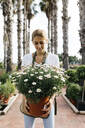 Female worker in a garden center holding a daisy plant - JRFF03533