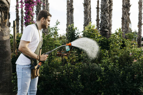 Spain, Tarragona. Worker of a garden center watering the plants in the afternoon. - JRFF03536