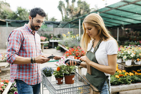 Customer paying with smartphone in a garden center - JRFF03539