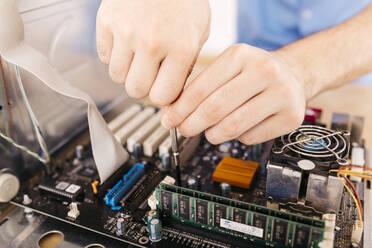 Close-up of technician repairing a desktop computer, using a screwdriver - JRFF03542