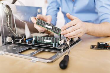 Close-up of technician repairing a desktop computer, changing the computer's RAM - JRFF03545