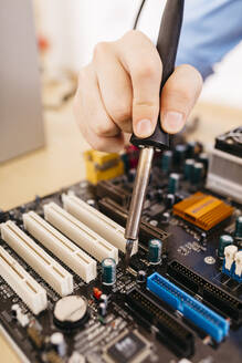 Close-up of technician repairing a desktop computer, soldering a component with tin - JRFF03560