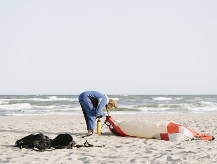 Male surfer preparing a kite on a beach - AHSF00713