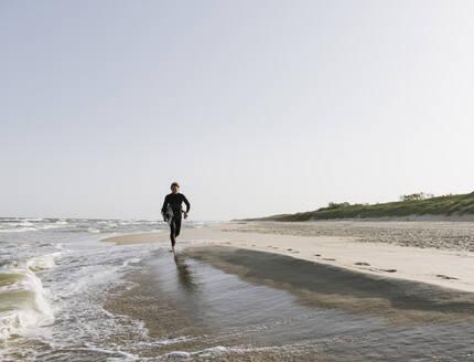Surfer running at the beach - AHSF00722
