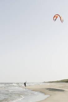 Kiteboarder prepairing his kite at the beach - AHSF00728