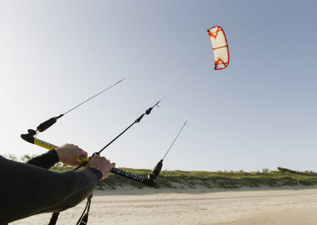 Arms of kiteboarder holding the kite - AHSF00731