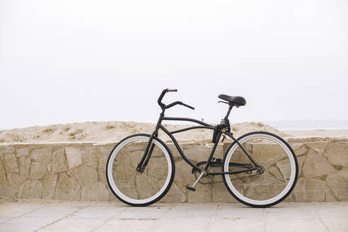 Bicycle resting on a wall on the beach - ACPF00563