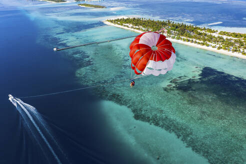 Aerial view of a paraglider flying along an atoll, South Male Atoll, Maldives - AMF07216