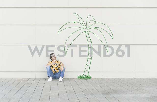 Digital composite of young man sitting at a palm at a wall - UUF18353 - Uwe Umstätter/Westend61