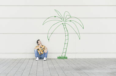 Digital composite of young man sitting at a palm at a wall - UUF18353