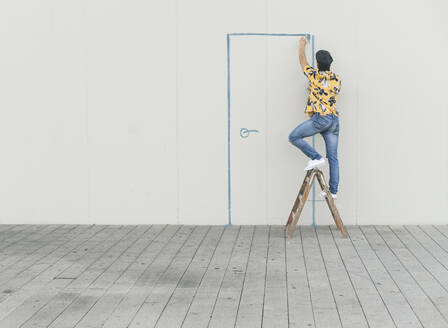 Digital composite of young man drawing a door at a wall - UUF18356