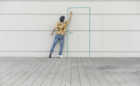 Digital composite of young man drawing a door at a wall - UUF18359