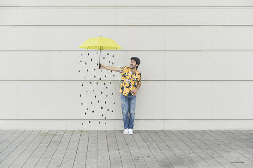 Digital composite of young man holding an umbrella at a wall with raindrops - UUF18362