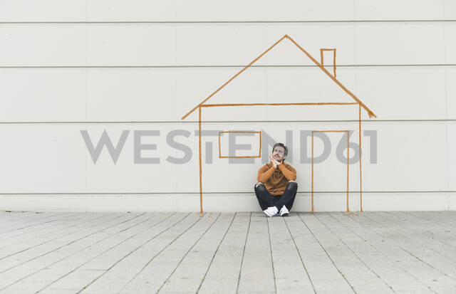 Digital composite of young man sitting at a wall with a house - UUF18365 - Uwe Umstätter/Westend61