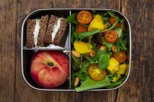 Lunchbox mit Mango-Salat (Ruccola, Spinat u.a. mit Mango und geröstetet Erdnüssen), Roggensaftbrot mit Frischkäse, Platt-Pfirsich - LVF08217