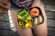 Midsection of girl having healthy lunch while sitting on bench - LVF08220