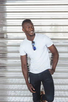 Portrait of confident young man wearing white t-shirt at a roller shutter - LJF00530