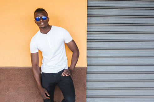 Portrait of young man wearing white t-shirt and sunglasses leaning against a wall - LJF00533