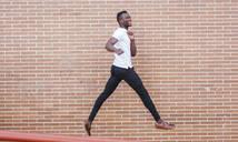 Young man wearing white t-shirt jumping at a brick wall - LJF00539
