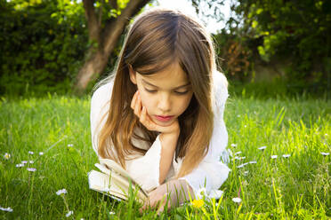 Girl lying on a meadow reading a book - LVF08225