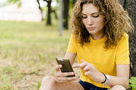 Young woman using cell phone in a park - GIOF06987