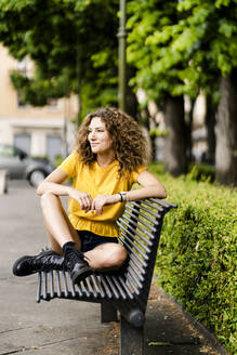 Smiling young woman sitting on a bench - GIOF06993