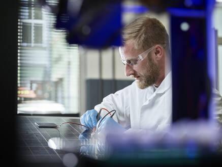 Technician measuring contact of silicon solar cell on solar panel - CVF01379