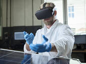 Technician with VR glasses and solar panel in lab - CVF01385