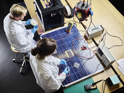 Two technicians working on 3d printed turbine wheel and solar panel in lab - CVF01400