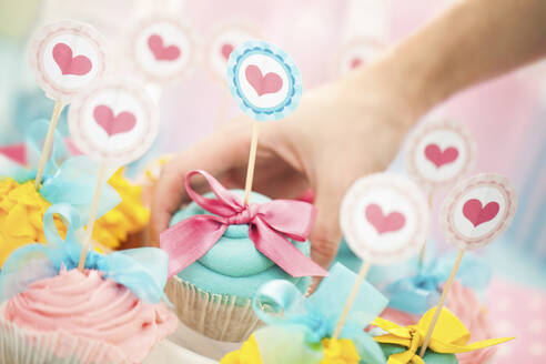 Close up of hand choosing cupcake at birthday party - BLEF12345