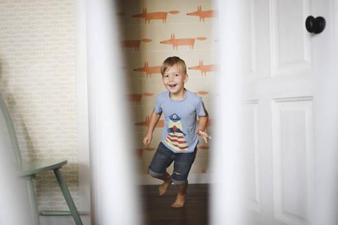 Happy boy running at home - EYAF00320
