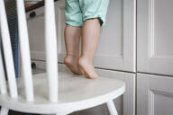 Little boy standing on tiptoes on chair in kitchen - EYAF00338