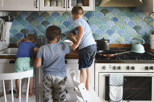 Russia, Moscow, three brothers cooking pan-cakes in the kitchen - EYAF00341