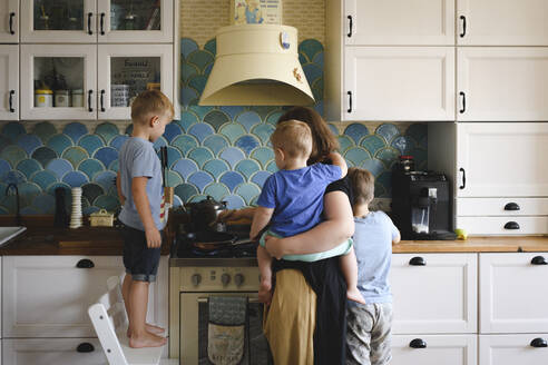 Russia, Moscow, young mother cooking with her three sons in the kitchen - EYAF00347
